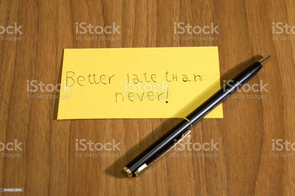 Better late than never handwrite on a yellow paper with a pen composition stock photo