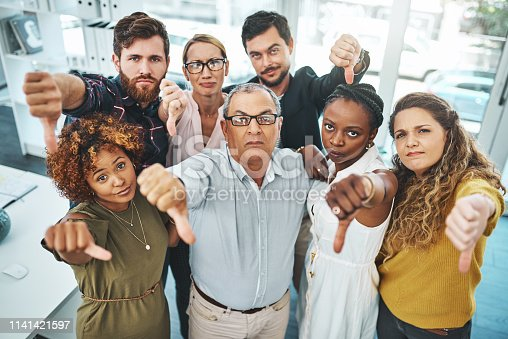 Portrait of a group of businesspeople showing thumbs down in an office