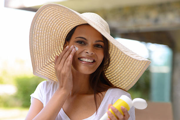 Better safe than sorry! An attractive young woman applying sunscreen to her facehttp://195.154.178.81/DATA/i_collage/pi/shoots/783592.jpg suntan lotion stock pictures, royalty-free photos & images
