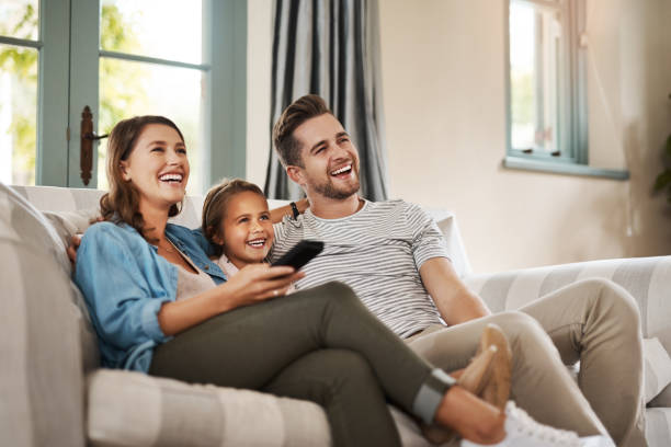 Better than the movie theatre Shot of a happy young family relaxing on the sofa and watching tv together at home watching tv stock pictures, royalty-free photos & images