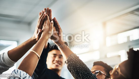 Shot of a group of unrecognizable businesspeople high fiving in an office