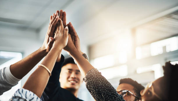 Better together Shot of a group of unrecognizable businesspeople high fiving in an office achievement stock pictures, royalty-free photos & images