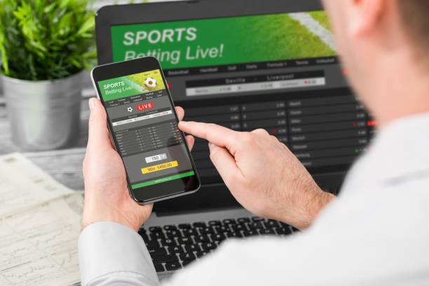 wetten wette sport telefonkonzept gamble laptop - online spiele spielen stock-fotos und bilder