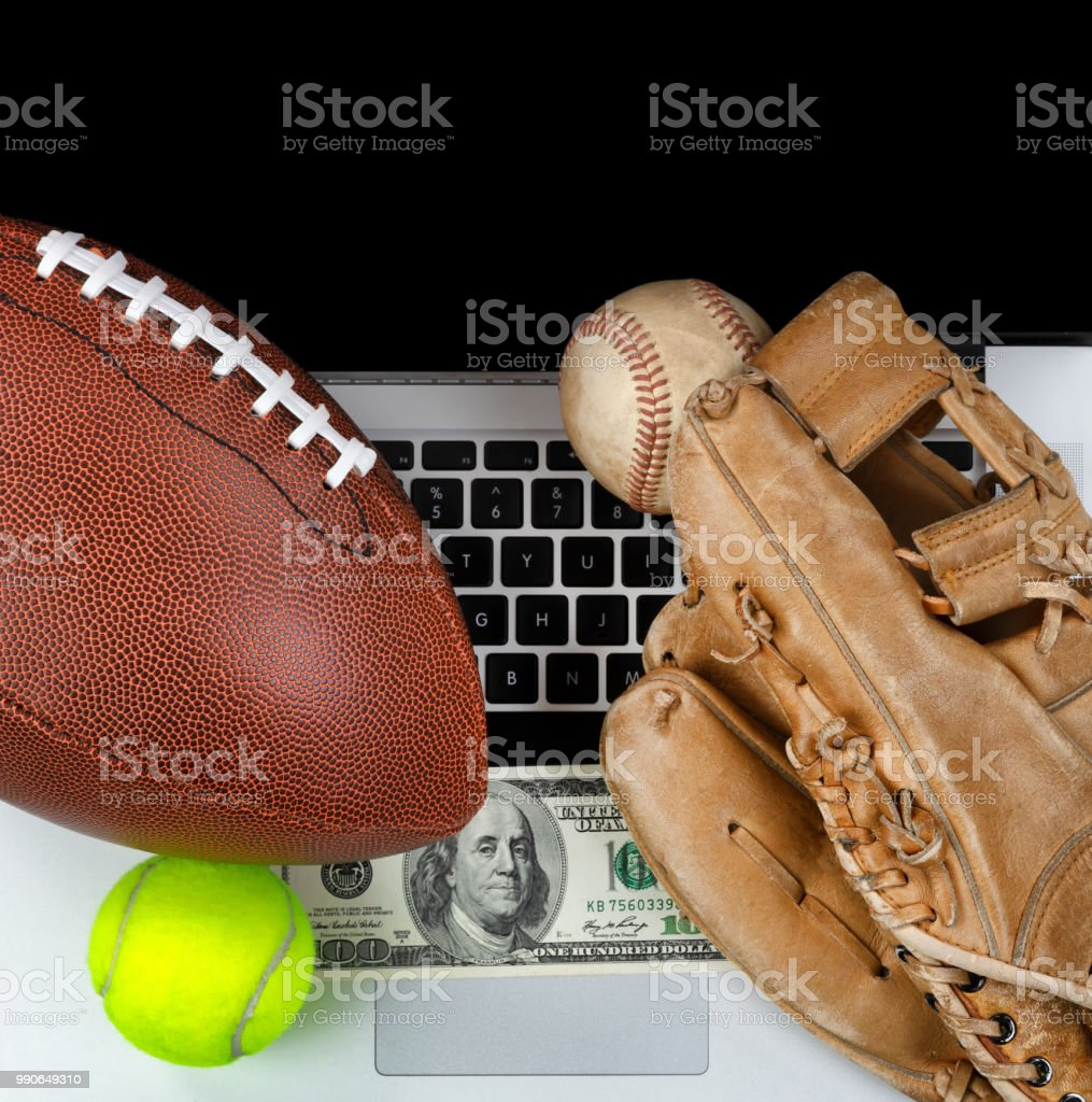 Betting on sports with computer and money in background stock photo
