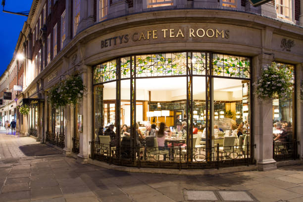 Betty's Cafe and Tea Rooms in York, UK St Helens Square, York, UK - SEPTEMBER 9, 2016. The exterior and window of the popular Betty's Cafe and Tea Rooms shown at night with a warmly lit interior. tea room stock pictures, royalty-free photos & images