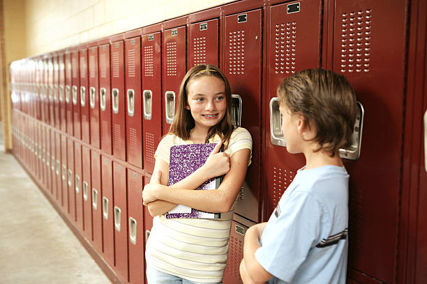 Between Classes A cute school girl talking to a boy outside her locker.   cute teen couple stock pictures, royalty-free photos & images