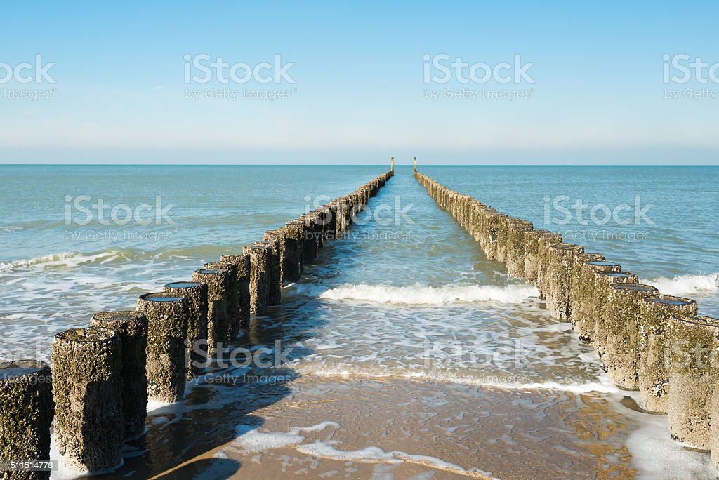 Between the two rows of poles of the breakwater stock photo