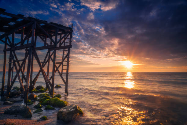 Beuatiful landscape scene with sun rays shot of a sunrise or sunset by the Black Sea near a wooden pontoon in Tuzla, Constanta Conty Romania stock photo