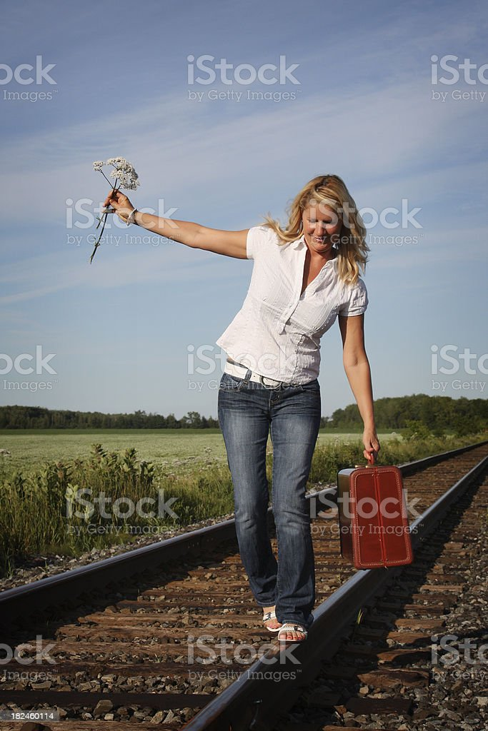 Beutiful matrue woman walking on a railroad track royalty-free stock photo