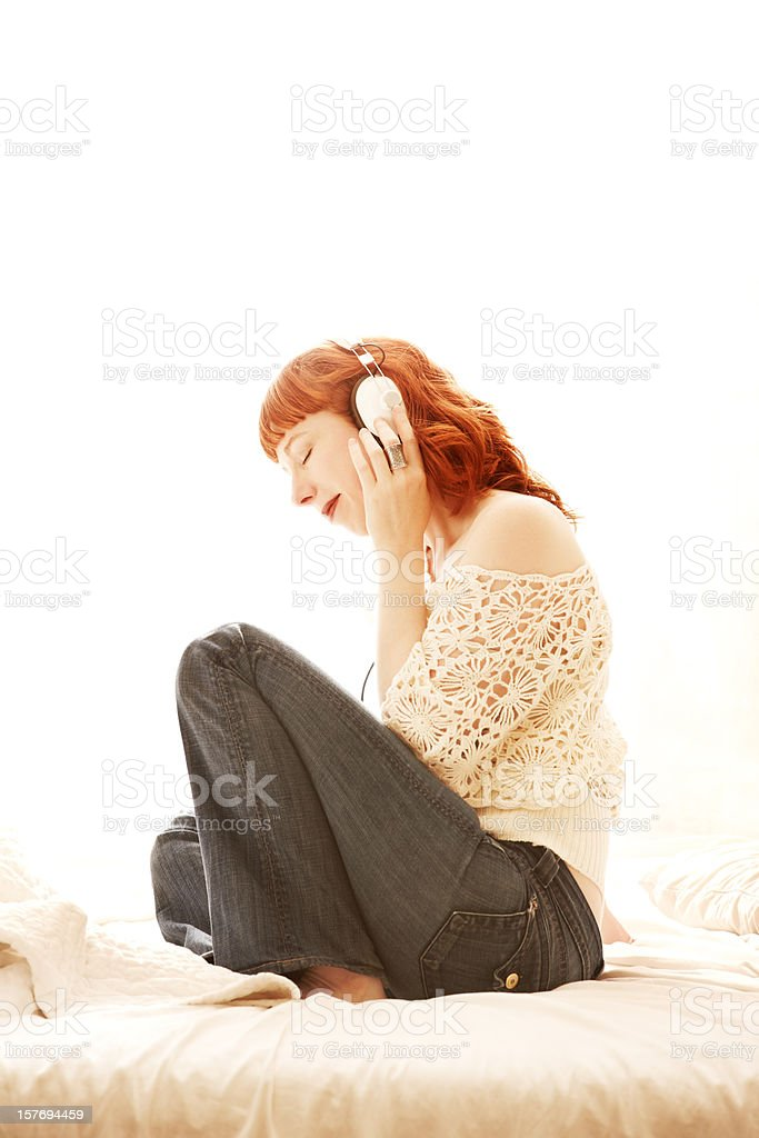 Beutiful redhead woman listening to headphones in bed stock photo