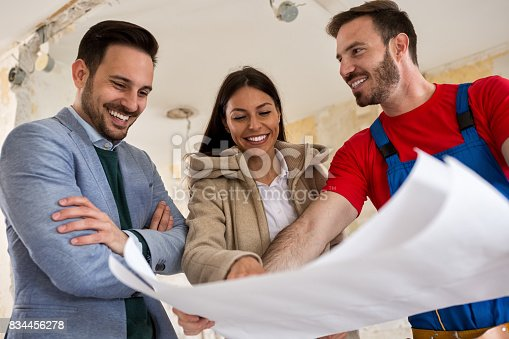 istock Beutiful young couple looking blueprints of their home with handyman 834456278