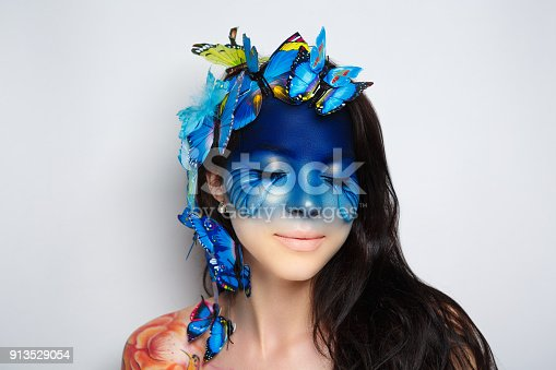 Bright blue butterflies seating on woman head, hair. Oriental beauty girl professional makeup. Portrait of a beautiful lady dark side of moon. Young girl close-up photo, creative art make-up facial