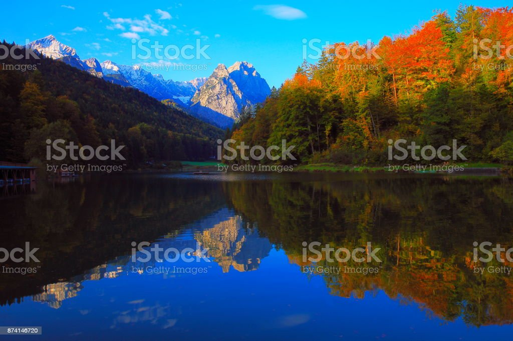 Beuty in nature: Riessersee alpine turquoise lake with reflection at gold colored sunrise, with Zugspitze, Waxenstein and Alpspitze view– dramatic landscape in Bavarian alps - Majestic alps in autumn, Snowcapped mountains – Garmisch, Bavaria, Germany stock photo