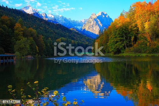 Beuty in nature: Riessersee alpine turquoise lake with reflection at gold colored sunrise, with Zugspitze, Waxenstein and Alpspitze view– dramatic Bavarian alps - Majestic alpine landscape in autumn, Snowcapped mountains – Garmisch, Bavaria, Germany