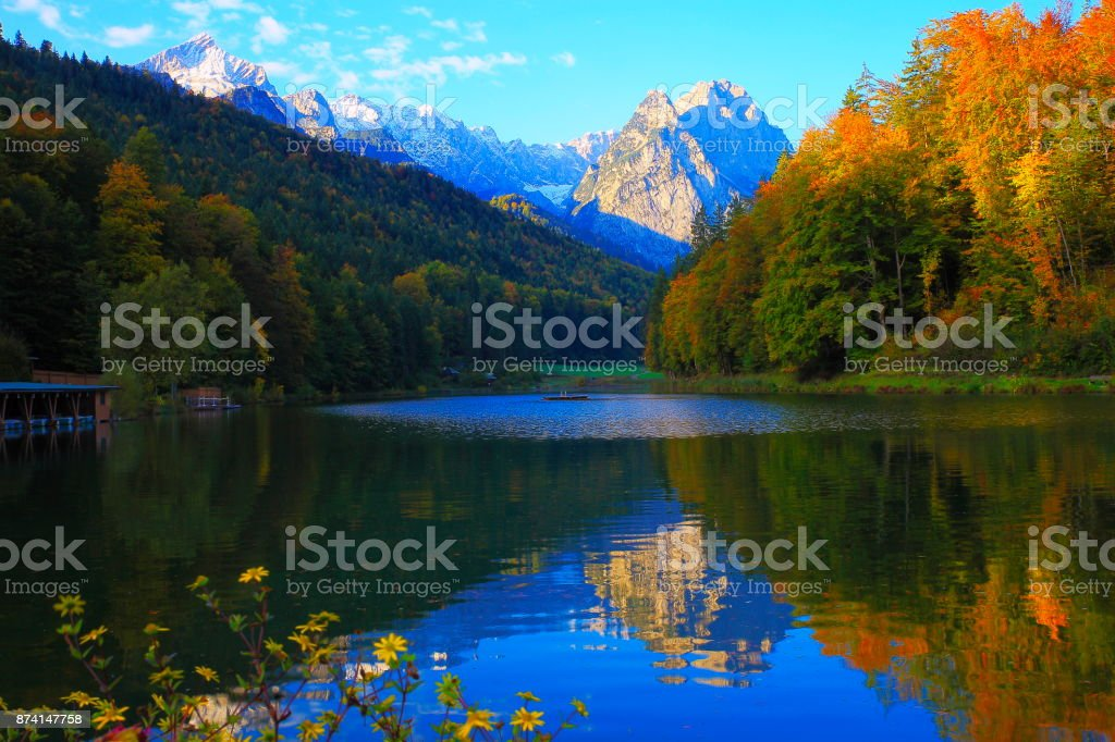 Beuty in nature: Riessersee alpine turquoise lake with reflection at gold colored sunrise, with Zugspitze, Waxenstein and Alpspitze view– dramatic Bavarian alps - Majestic alpine landscape in autumn, Snowcapped mountains – Garmisch, Bavaria, Germany stock photo