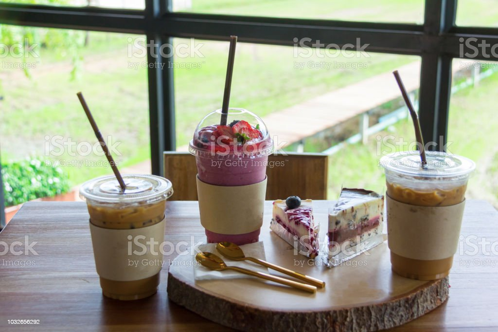 beverage set of iced coffee blueberry cake and smoothie in wood table at cafe stock photo