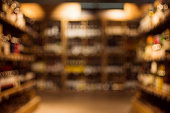 Different beverages are on shelves in illuminated drink store, blurred or defocused background.