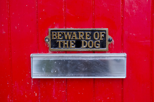 Beware of dog sign on large red house front door for home security