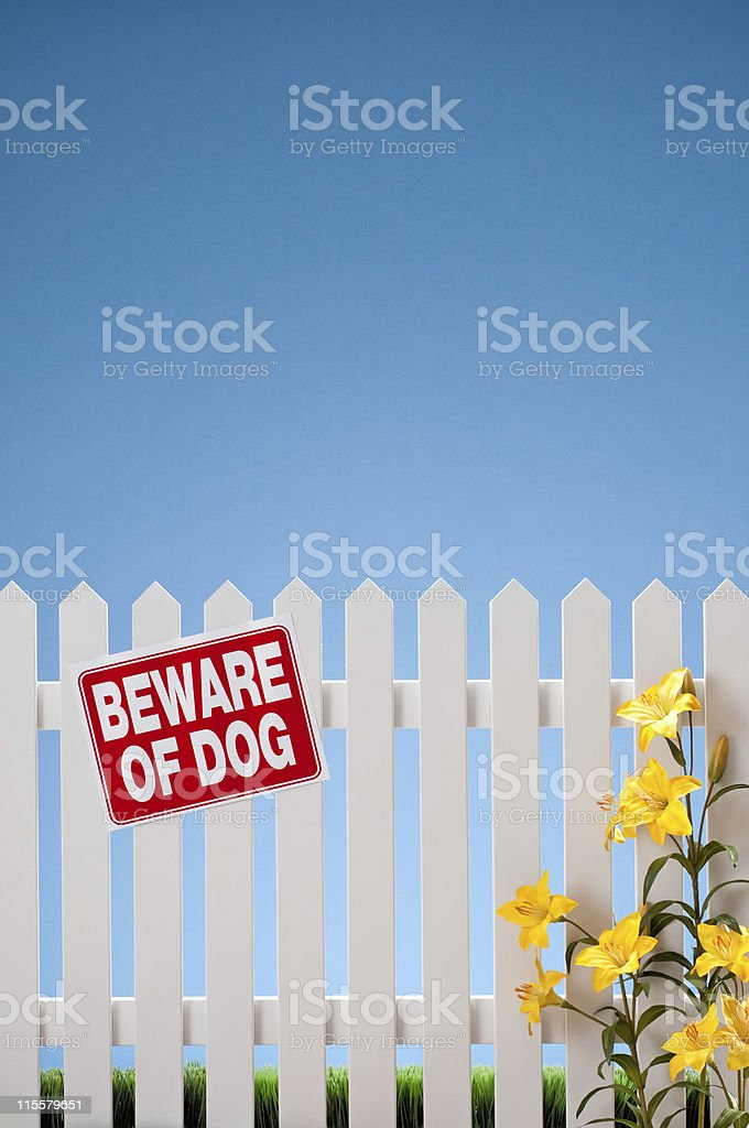 Beware Of Dog Sign On White Picket Fence royalty-free stock photo