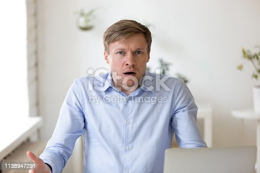 857213750istockphoto Bewildered businessman throwing up his hands at workplace 1138947291