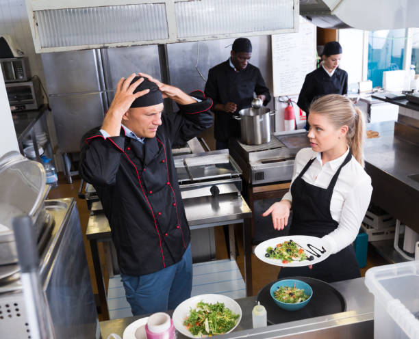 Desnorteado chef falando com garçonete - foto de acervo