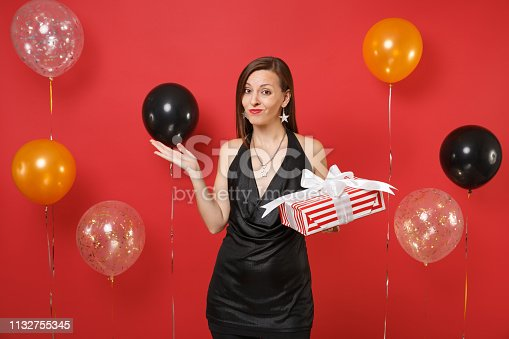istock Bewildered irritated girl in black dress spreading hands, holding red box with gift, present on bright red background air balloons. Women's Day, Happy New Year, birthday mockup holiday party concept. 1132755345