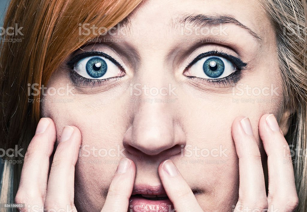 Bewildered young woman brings her hands at the face stock photo