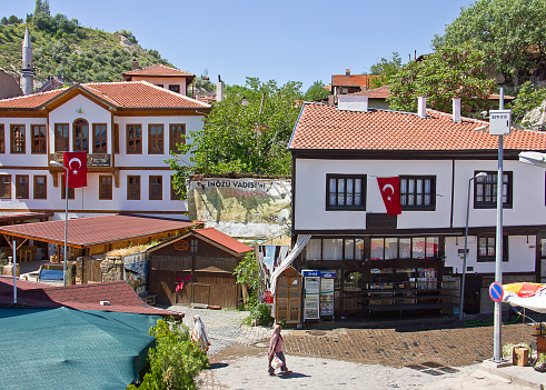Ankara, Turkey - May 20, 2016: Public streets of Beypazarı with traditional Turkish buildings which are now restaurants. People are sitting in the cafes and others walking in the street. There are gift shops in the street. Beypazarı is a touristic town of capital Ankara.