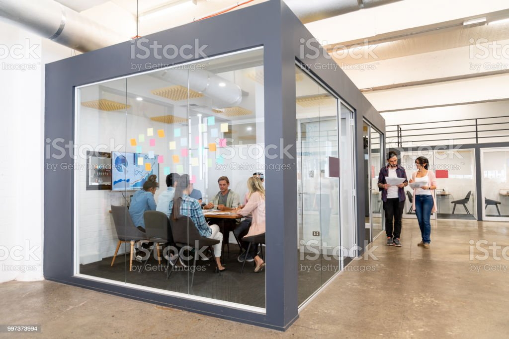 BGroup of people in a business meeting at a creative office Group of people in a business meeting at a creative office sharing ideas - teamwork concepts. **IMAGE ON SCREEN WAS DESIGNED FROM SCRATCH BY US** Adult Stock Photo