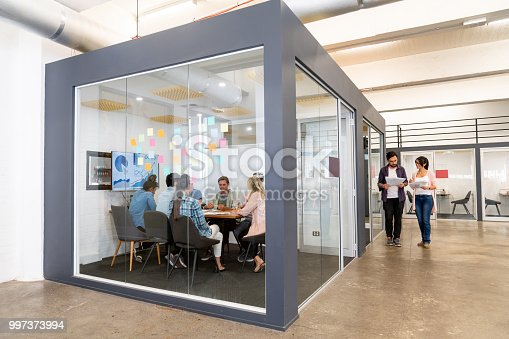 Group of people in a business meeting at a creative office sharing ideas - teamwork concepts. **IMAGE ON SCREEN WAS DESIGNED FROM SCRATCH BY US**