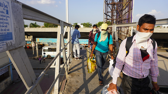 Indian migrant workers during COVID 19 Corona Virus nationwide lockdown returning back home via special trains or Bus. Social distancing and wearing masks at the Railway station. Indian Police on duty.