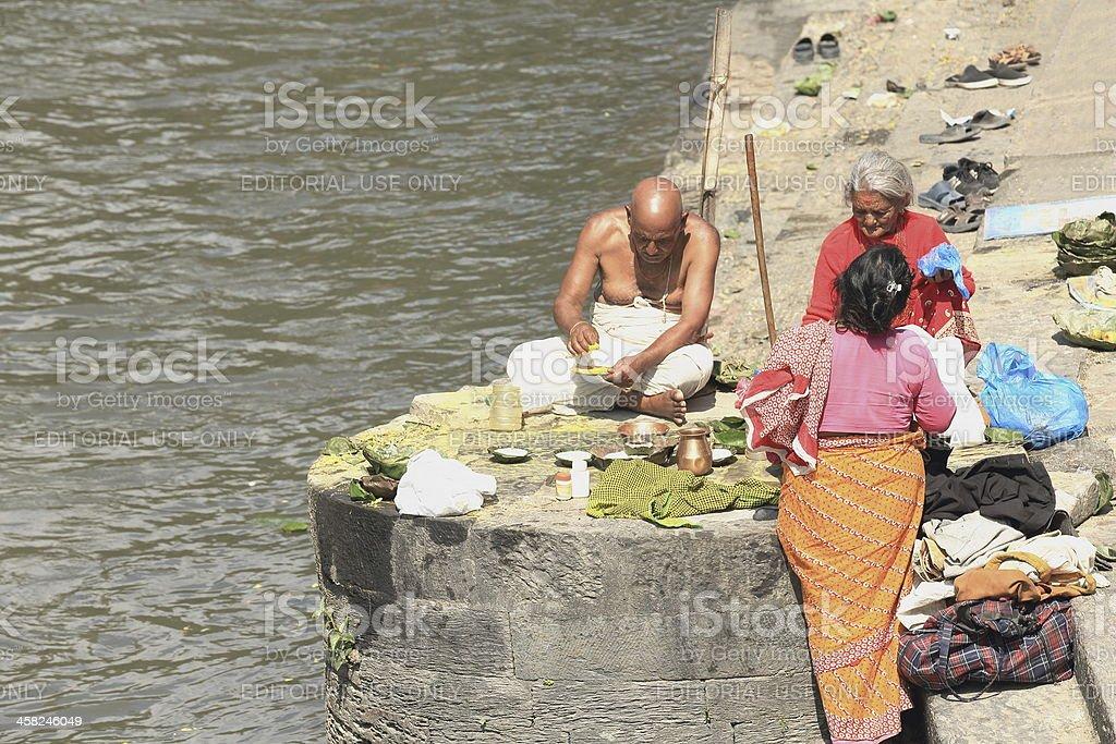 Bhatta priest-two faithful women. Pashupatinath temple-Bagmati river-Deopatan-Kathmandu-Nepal. 0288 stock photo