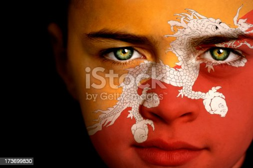 Portrait of a boy with the flag of Bhutan painted on his face