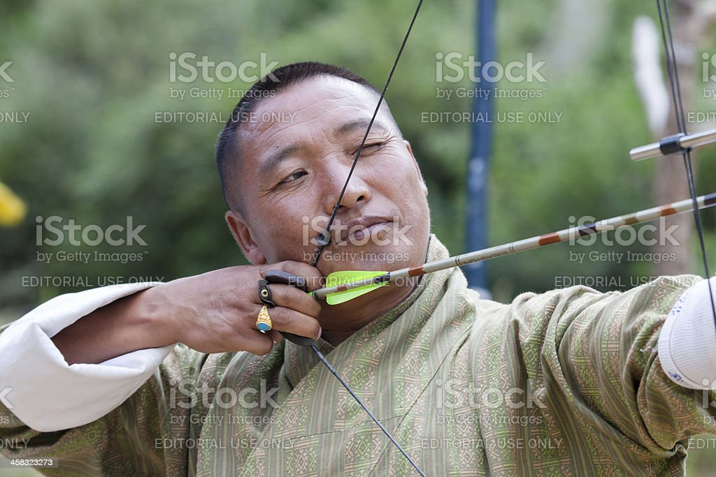 Bhutanese man  aims arrow in archery competition foto