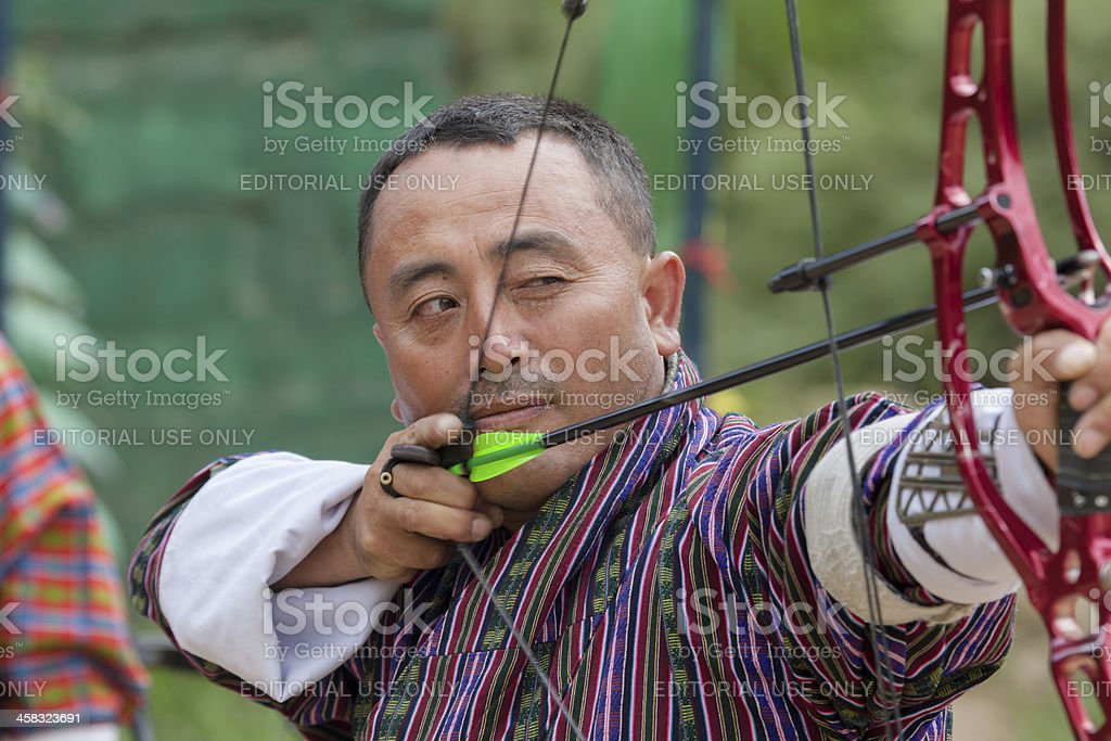 Bhutanese man  aims arrow in archery competition royalty-free stock photo