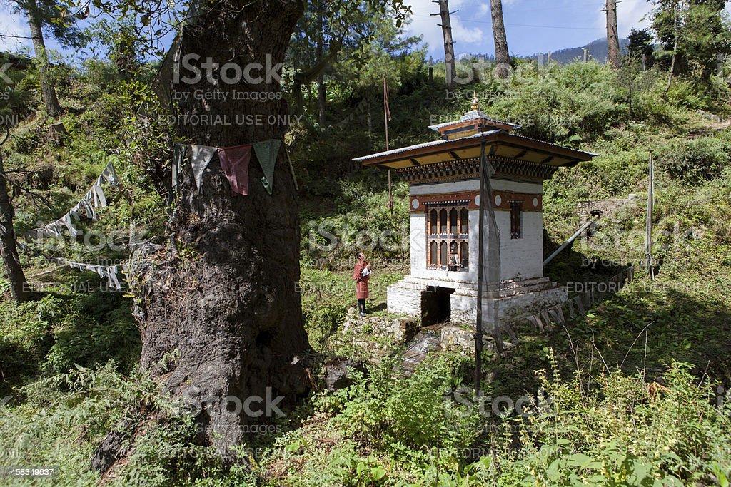 Bhutanese man prays in front of stupa with prayer wheel foto
