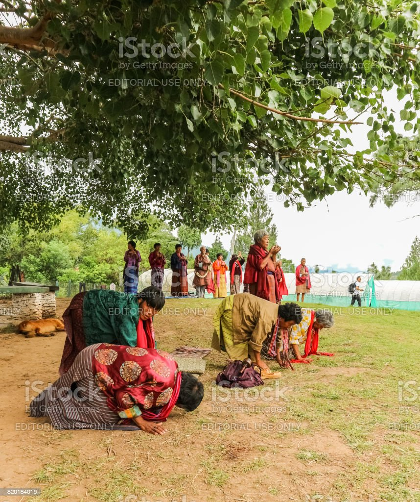 Bhutanese people  in tradtional dress praying in Thimphu, Bhutan stock photo