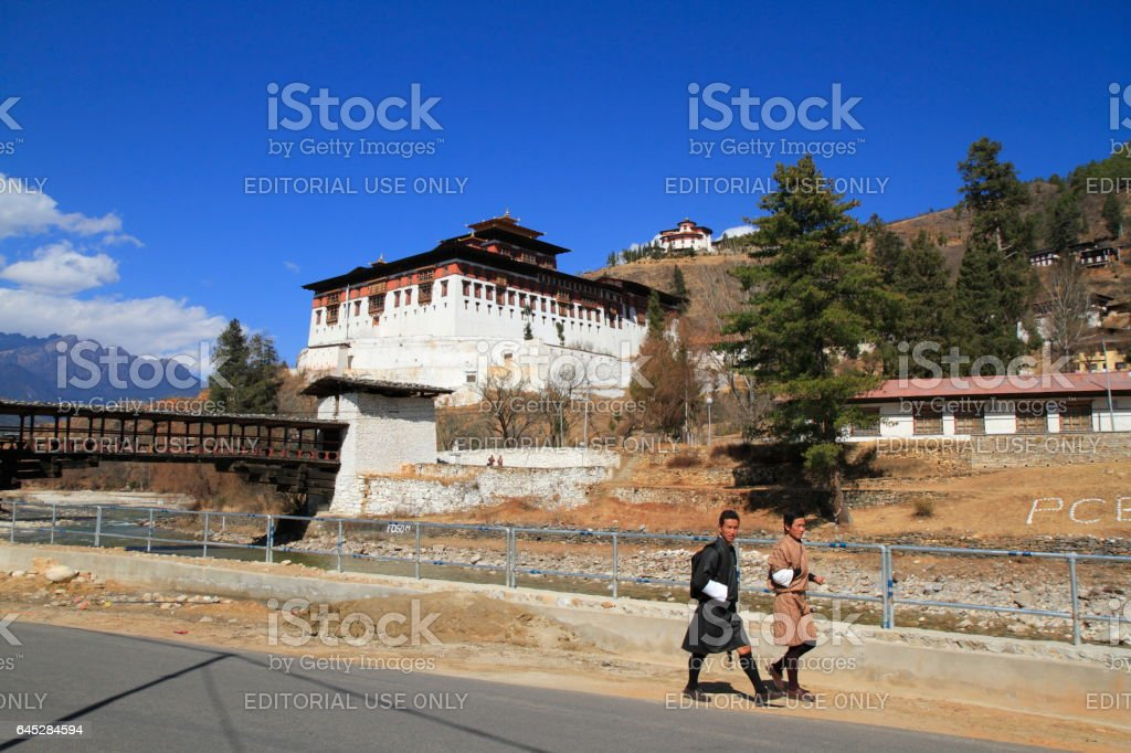 PARO, BHUTAN - FEBRUARY 20, 2014: Bhutanese young man in traditional clothes walk on the street before Paro Rinpung Dzong castle stock photo