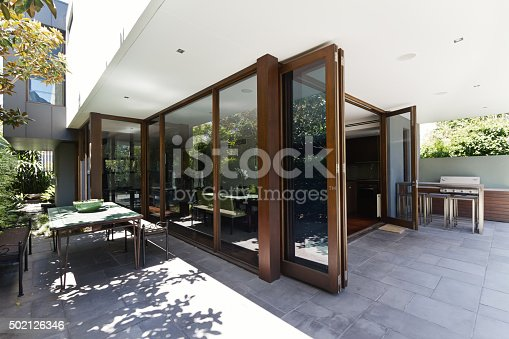 istock Bi fold doors opening to rear courtyard of contemporary home 502126346