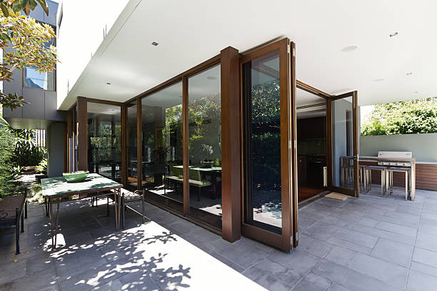 Bi fold doors opening to rear courtyard of contemporary home Bi fold doors opening up to rear courtyard of contemporary Australian home foldable stock pictures, royalty-free photos & images