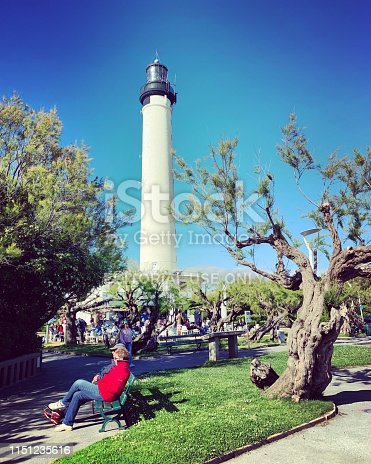 Biarritz, France - May 2019: Phare de Biarritz, Biarritz Lighthouse and people enjoying sunny day in a park