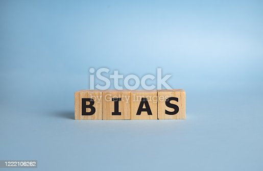 Bias - word from wooden blocks with letters, personal opinions prejudice bias concept, blue background.