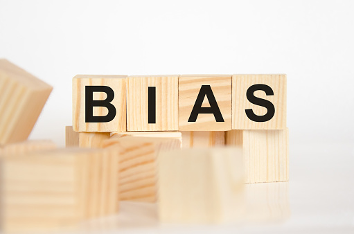 istock Bias - word from wooden blocks with letters, personal opinions prejudice bias concept, random letters around, white background 1263939831