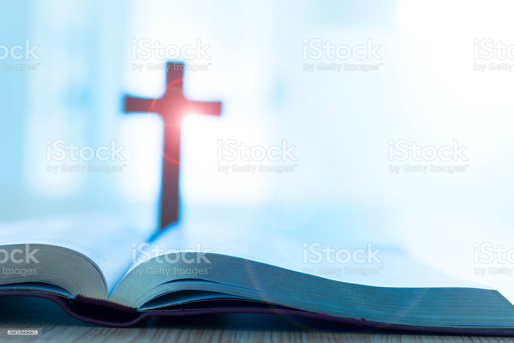 Bible and cross on desk stock photo