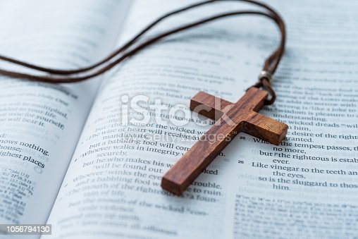Bible and cross on wooden desk.