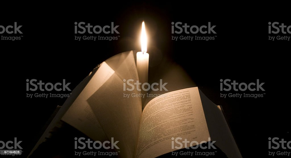 Bible book pages in front of a candle royalty-free stock photo