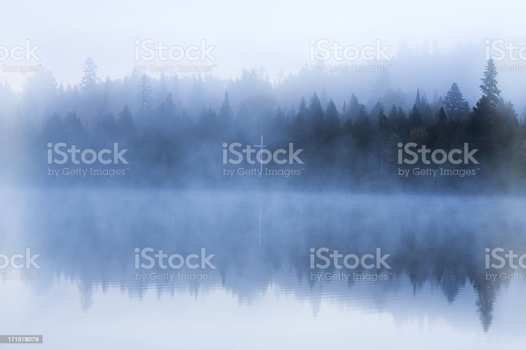 Bible camp cross on foggy shore stock photo