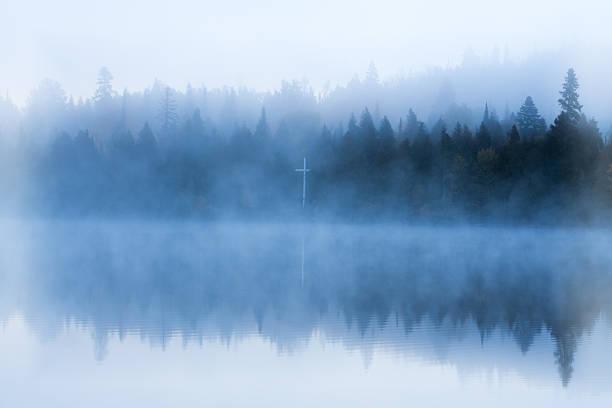 Bible camp cross on foggy shore stock photo