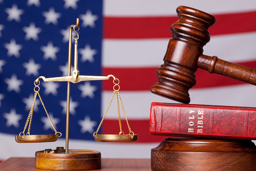 Bible, gavel and scales of justice on american flag background.The focus in on the objects.The flag background is blurred.Bible is placed under the gavel.Horizontal frame, shot with a full frame DSLR camera.