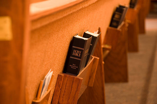 Bible in a pew Holy Bible being held in a shelf on the back of a pew in a church pew stock pictures, royalty-free photos & images